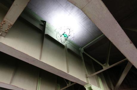 暗い橋桁の下を照らしながら、画像を撮影するドローンの様子